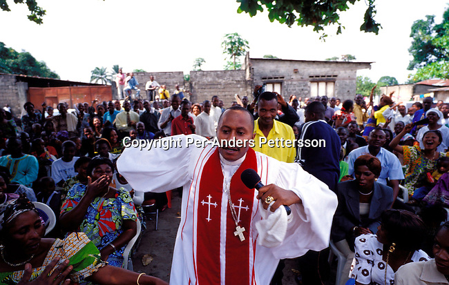 dicocon00190.Congo. King Shasa. Religion. Christianity. Kutino Fernando, a priest and the leader of ÒArmee de VictoireÓ, Victory army church of God, one of biggest and most popular churches in Kinshasa with his congregation on February 29, 2002 in central Kinshasa, Congo. So popular that people can't get in and hundreds of people stand outside. These churches have grown the last years as people are looking for solutions to their problems..©Per-Anders Pettersson/iAfrika Photos