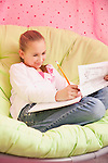USA, Illinois, Metamora, Girl (10-11) sitting on soft chair and writing