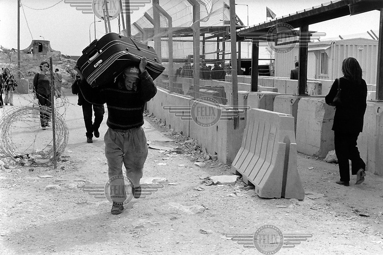 A porter carries a suitcase across the Qalandiya checkpoint.