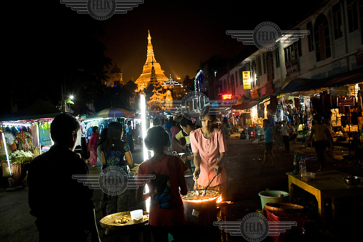 Street vendors prepare and sell food on a market near the Buddhist Shwedagon Pagoda (also known as the Great Dagon Pagoda) in Rangoon (Yangon) at night. .