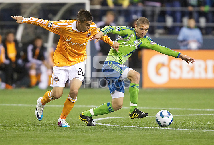 Houston Dynamo midfielder Geoff Cameron battles Seattle Sounders FC defender Osvaldo Alonso  during play at Qwest Field in Seattle Friday March 25, 2011. The match ended in a 1-1 draw.