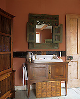 A washbasin is set in a wooden cupboard in a rustic style bathroom.