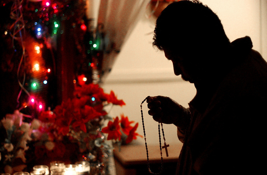 Journal photo by Ted Richardson:  12/11/2004  An Afro-Mexican worships the Virgin of Guadalupe at Lakeside Apartments during La Cuarentena, a 40-day celebration of the appearance of the Virgin to Juan Diego.