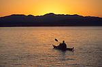 A young man paddles a sea kayak at sunrise on Jackson Lake in Grand Teton National Park, Jackson Hole, Wyoming.