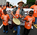 Ed Brown plays a djembe drum, while brothers Demetrius Riggans,11 (left) and Sanford Riggans, 9, keep rhythm with drumsticks as they walk in the Wear Orange Day March against gun violence on Saturday June 2, 2018. June is National Gun Violence Awareness Month.<br /> Photo by Tim Vizer