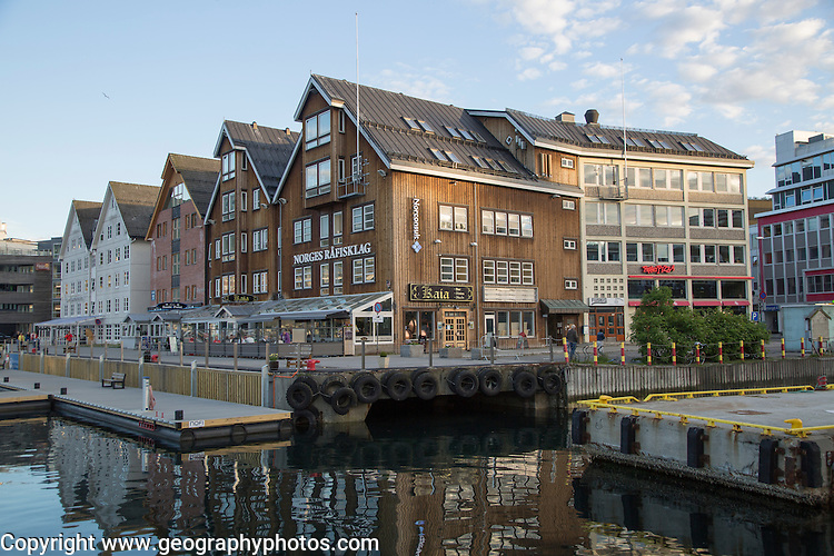 Historic wooden buildings bars and restaurants along harbour waterside,  Tromso, Norway