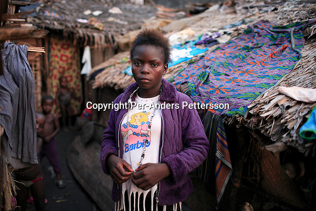MBANDAKA, DEMOCRATIC REPUBLIC OF CONGO APRIL 12: Nicolette Bopunza, age 14, a young prostitute stand outside her house on April 12, 2006 in the port in Mbandaka, Congo, DRC. She lives and works in the port, and she stays with three other girls in the same age in a small room. Nicolette and her friends charge about 50 cents for sex and about US$ 2 for a whole night. Their clients are mainly dockworkers and crewmembers on visiting boats. The Congo River is a lifeline for millions of people, who depend on it for transport and trade. Congo is planning to hold general elections by July 2006, the first democratic elections in forty years..(Photo by Per-Anders Pettersson/Getty Images)..
