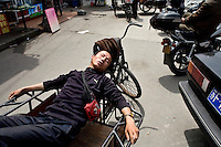 Deliverymen sleep on their cargo bikes outside a fake designer clothing market in Shanghai, China.