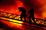 SOUTH Windsor firefighters climb the their ariel ladder as heavy fire pours from the roof, Wednesday night on Mill Pond Drive in South Windsor where 10 units were heavily damaged or destroyed in the blaze. A Jim Michaud pic 9/11/02