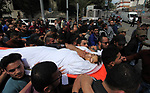 Relatives carry the body of a Palestinian man, who was killed in an Israeli airstrike, during his funeral in Gaza city on May 5, 2019. One Israeli man and eight Palestinians, including a pregnant woman and her infant niece were killed so far since tensions ratcheted up along the border on Friday. Three Israelis were wounded as rockets fell on the Israeli south on Saturday. Photo by Mahmoud Ajjour