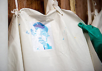A bleached image of a health care worker Joseph W. Walatee on a reusable apron. Labels are meant to be torn off and discarded during the meticulous doffing process, but this one went through the bleaching process in which items are soaked in a strong bleach solution. Most health care workers use disposable aprons at the ELWA II ETU (Ebola treatment unit) in Monrovia, Liberia. Tuesday, March 3, 2015. The ETU, operated by ELWA Hospital, was the first to open in Monrovia. Occidental College professor Mary Beth Heffernan's PPE Portrait Project involves creating wearable portraits of health care workers who must wear PPE (personal protective equipment) when working with patients, for example, patients with Ebola. <br /> (Photo by Marc Campos, Occidental College Photographer) Mary Beth Heffernan, professor of art and art history at Occidental College, works in Monrovia the capital of Liberia, Africa in 2015. Professor Heffernan was there to work on her PPE (personal protective equipment) Portrait Project, which helps health care workers and patients fighting the Ebola virus disease in West Africa.<br />