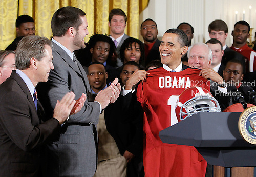 United States President Barack Obama (R) receives a jersey as head coach Nick Saban (L) and offenisve line Mike Johnson (2nd L) look on during an East Room event to host members of the Alabama Crimson Tide, Monday, March 8, 2010 at the White House in Washington, DC. Obama welcomed the 2009 BCS Champions to honor its 13th championship and an undefeated season.  .Credit: Alex Wong - Pool via CNP