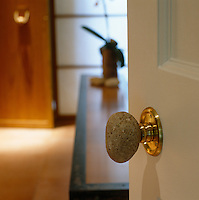 This doorknob is fashioned out of a large pebble attached to a more traditional brass fixture