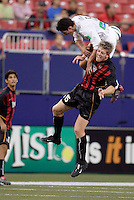 The Revolution's Jay Heaps goes over the top of the MetroStars' John Wolyniec while going for a header. The New England Revolution were defeated by the MetroStars 3 to 2 on Saturday September 11, 2004 at Giant's Stadium, East Rutherford, NJ..
