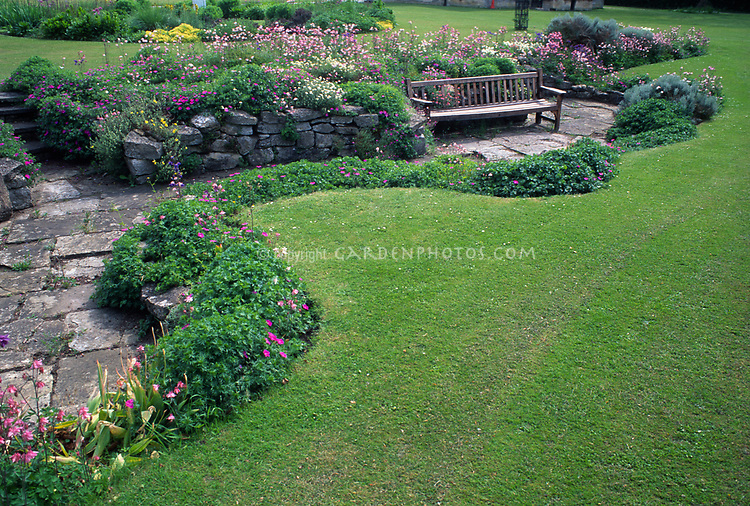 Curving lawn and perennial beds with patio and bench, stone wall, sloped site with tiers