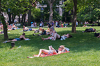 New Yorkers and visitors lounge on the lawn in Washington Square Park in Greenwich Village in New York on Tuesday, June 13, 2017. Temperatures have breached the 90 degree mark in the city for three days in a row making it officially a heat wave. ( © Richard B. Levine)