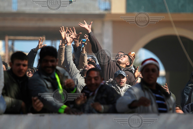 Refugees reach for bread and supplies thrown over the border wall from Tunisa to Libya. Tens of thousands of people, mainly Egyptian workers, fled unrest in Libya and crossed the border into Tunisia. Some slept in the open for several days before being processed.  At the same time forces loyal to Col. Gaddafi fought opposition forces in various parts of the country.