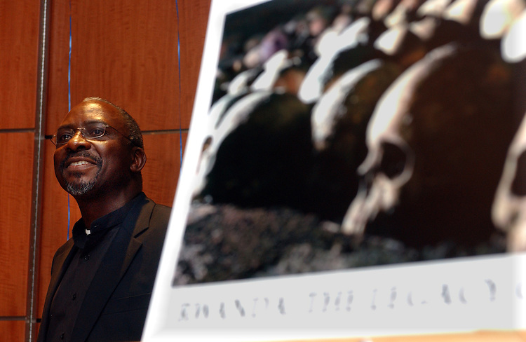 Dele Olojede speaking at a celebration in Auditorium at Newsday's offices in Melville on Monday April 4, 2005, for his winning of the Pulitzer Prize for International Reporting by a series of articles he wrote on Rwanda. In the foreground is one of the photographs that were taken by Newsday Photographer J. Conrad Williams, Jr. to illustrate the articles. (Newsday Photo / Jim Peppler).