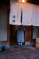 A kimono clad waitress waits at the doorway of a Gion restaurant to welcome guests, Kyoto.