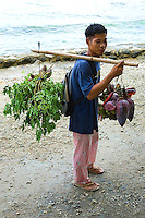 Banana flowers are used by Filipinos and most Asians for cooking and as a garnish for meals. Filipino vendors roam around town early morning peddling their wares such as this man with his yoke.