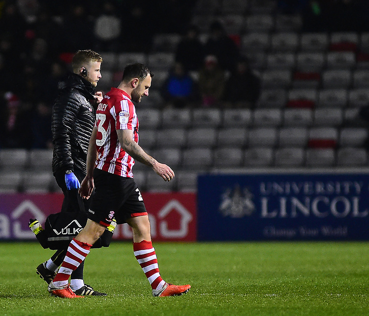 Lincoln City's Neal Eardley leaves the pitch with an injury, with Lincoln City's head of sports science and medicine Mike Hine<br /> <br /> Photographer Andrew Vaughan/CameraSport<br /> <br /> The EFL Sky Bet League Two - Saturday 15th December 2018 - Lincoln City v Morecambe - Sincil Bank - Lincoln<br /> <br /> World Copyright © 2018 CameraSport. All rights reserved. 43 Linden Ave. Countesthorpe. Leicester. England. LE8 5PG - Tel: +44 (0) 116 277 4147 - admin@camerasport.com - www.camerasport.com