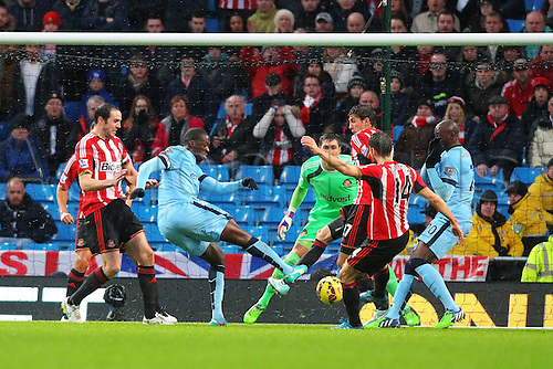 01.01.2015.  Manchester, England. Barclays Premier League. Manchester City versus Sunderland. Manchester City midfielder Yaya Toure shoots at goal under pressure from O'Shea and Gomez of Sunderland