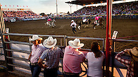 Spectators watch a display of horsemanship at a Sunday evening rodeo in Dodge City, Kansas.