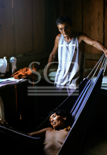 Ipixuna village, Amazon, Brazil. Funai doctor with an Arawete patient in a hammock in the village health post.
