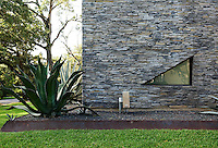 A raised metal flowerbed surrounds the house and is planted with large aloe vera amongst gravel