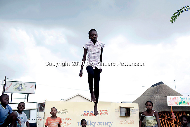 SOWETO, SOUTH AFRICA: Girls play on a trampoline on a street corner in Soweto, South Africa. Soweto is the largest township in South Africa, located about 10 kilometers southwest of downtown Johannesburg. The population is estimated to be around 2-3 million. (Photo by Per-Anders Pettersson)