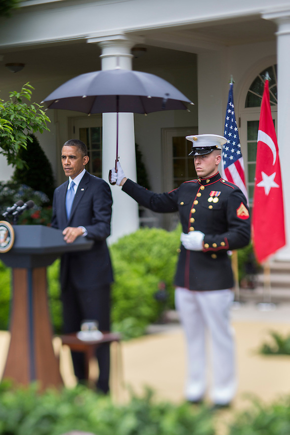 U.S. President Barack Obama is shielded from  rain by a U.S. Marine holding an umbrella during a joint news conference with Turkish Prime Minister Recep Tayyip Erdogan in the White House Rose Garden in Washington.