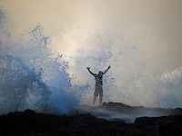 A man stands with outstretched arms while a wave splashes him, Kailua Kona, Big Island.