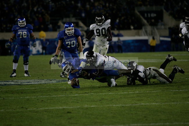 UK quarterback Morgan Newton gets tackled by two Mississippi State Bulldogs during the game at Commonwealth Stadium on Saturday, Oct. 31, 2009. Photo by Adam Wolffbrandt | Staff