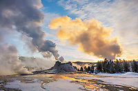 Yellowstone National Park, WY: Steam venting from Castle Geyser with winter sunrise light on Old Faithful plume.