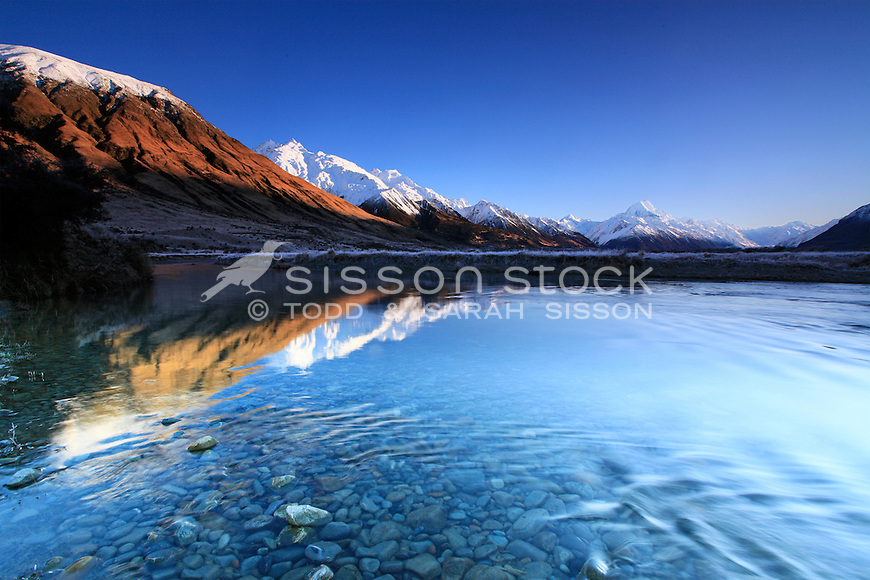 Sunrise reflection on the Tasman river. Southern Alps seen in the background