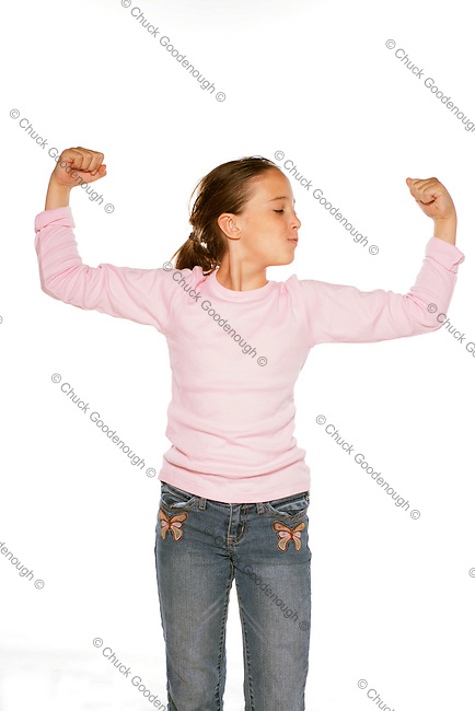 Stock Photo showing a Pre-Teen Girl Making a Muscles with both arms using all her might.