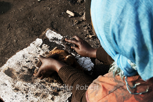 A woman cleans a sheep head, to be cooked and sold, in Langa. April 2009