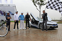 Marco Kaussler waves the flag as Paul McGinley (IRL) and Justin Rose (ENG) take to the tandem bike against Ian Poulter (ENG) and Wu Ashun (CHN) in the BMW i8 for a challenge during Wednesday's Pro-Am Day of the 2014 BMW Masters held at Lake Malaren, Shanghai, China 29th October 2014.<br /> Picture: Eoin Clarke www.golffile.ie
