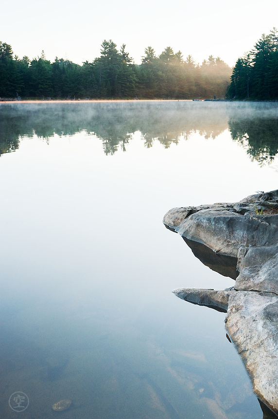 The sunrise breaks through the forested far shore, reflecting the trees on the still waters of Balsam Lake. In the foreground the granite shore drops steeply into the water.
