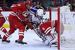 20 December 2014: New York's Derick Brassard (16) tries to jam the puck past Carolina's Cam Ward (30) as Victor Rask (SWE) (49) tries to push him away. The Carolina Hurricanes played the New York Rangers at the PNC Arena in Raleigh, North Carolina in a 2014-15 National Hockey League game. Rangers won the game 3-2 after winning the shoot out 1-0 after overtime.