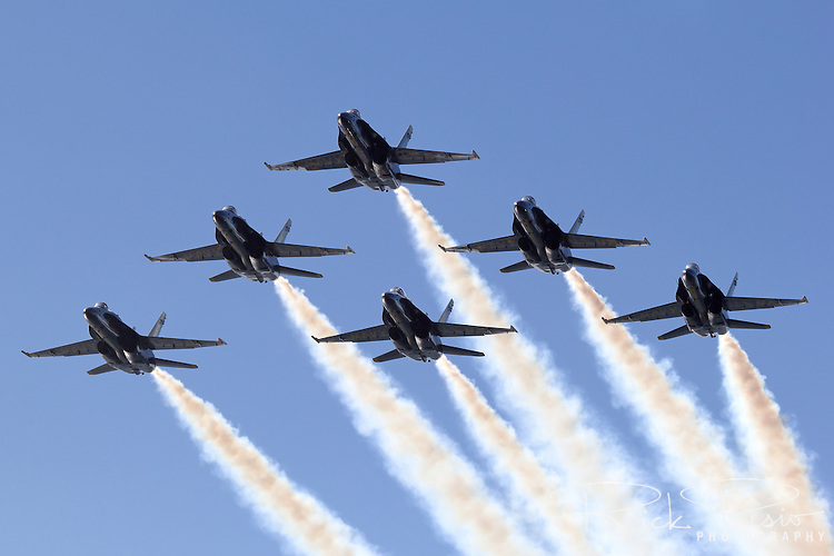 Blue Angels pass overhead in a delta formation.