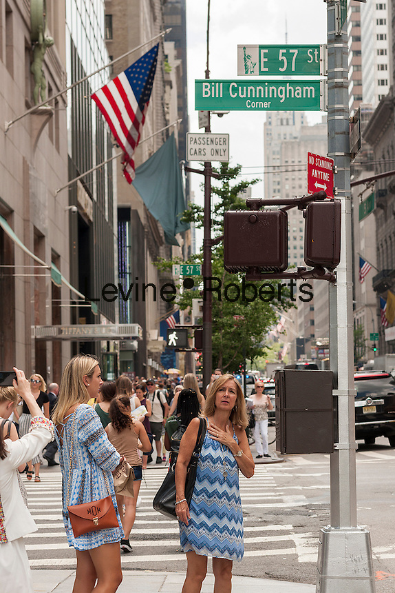 The stylish and the frumpy pay homage to Bill Cunningham and view the temporary sign at the corner of 57th Street and Fifth Avenue which renames the street corner in honor of the iconic street fashion photographer, seen on Wednesday, July 6, 2016. The 87-year old Cunningham, known for his photographs of street fashion, died on June 25. (© Richard B. Levine)