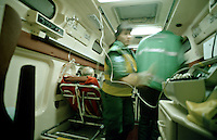 Paramedic ambulance crews with patients in ambulance