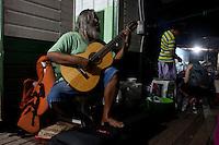 Vila Progresso.<br /> <br /> Rubens Gomes no violão  e Warwick Manfrinato  na flauta véspera do III Encontrão.<br /> <br /> Com a criação da Convenção sobre Diversidade Biológica - CDB -  tratado da Organização das Nações Unidas,  e a ratificação do protocolo de Nagoia em  2010,   se inicia um processo de organização para os  Povos e Comunidades Tradicionais em  busca de maior  qualidade de vida não apenas na Amazônia, mas em todo  mundo. <br /> <br /> Assim, em dezembro de 2013 a Rede Grupo de Trabalho Amazônico – GTA, em parceria com a Regional GTA/Amapá, o Conselho Comunitário do Bailique, Colônia de Pescadores Z-5, IEF, CGEN/DPG/SBF/MMA, juntamente com 36 comunidades do Arquipélago do Bailique, inicia o processo de criação do primeiro protocolo comunitário na Amazônia, instrumento que regula relações comerciais amparado por leis ambientais, estabelecendo o mercado justo, proteção da biodversidade,  entre outros . <br /> <br /> Desta forma, após dezenas de encontros, debates e oficinas,  as Comunidades Tradicionais do Bailique, articuladas pelo GTA,  se reuniram durante os dias 26, 27 e 28 de fevereiro, onde os moradores, em assembléia geral ordinária, definiram sua personalidade jurídica   criando uma associação para atuação comercial, votando seu estatuto e estabelecendo os diversos grupos de trabalho necessários para a gestão do Protocolo Comunitário.<br /> <br /> O encontro na comunidade São João Batista no furo do macaco(igarapé que dá acesso a vila), foz do Amazonas, recebeu cerca de 100 lideranças de 28 comunidades  nestes dias , que chegavam de barcos e canoas acompanhados por suas famílias<br /> <br /> Durante o debate,  representantes  do Ministério do Meio Ambiente, Ministério Público Federal, Fundação Getúlio Vargas, Embrapa e Conab esclareciam dúvidas e indicavam caminhos para fortalecer o primeiro protocolo comunitário na Amazônia.<br /> Arquipélago do Bailique, Vila Progresso, Macapá, Amapá, Brasil.<br /> Foto Paulo Santos