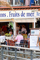 Restaurant guests eating outside. Sign with Fruit de mer, seafood. Collioure. Roussillon. France. Europe.