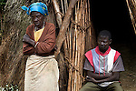 Members of the family of rape victim Bora Namutu aged 18yrs standing in the doorway of their village hut in Kaniola area.  Bora was raped at night in the hut.  The whole family has been affected.  The rebels come down at night to raid the villages, rape and abduct women. <br />
