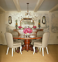 Grisaille murals painted by Patrice Yourdon grace the walls of this dining room with a 19th century circular table and an Italian bed crown made into a chandelier