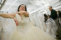 "Bride-to-be Michele Sarnecky (L) tries on a discounted wedding dress during the annual ""Running of the Brides"", a a first-come-first-served bridal gown sale, at the Filene's Basement store in New York City, USA, 3 March 2006."