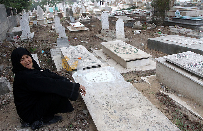 A Palestinian woman visit her relatives graves on the first day of Eid al-Adha in Gaza city on Nov.16,2010. Muslims around the world celebrate Eid al-Adha to mark the end of the haj by slaughtering sheep, goats, cows and camels to commemorate Prophet Abraham's willingness to sacrifice his son Ismail on God's command. Photo by Ashraf Amra