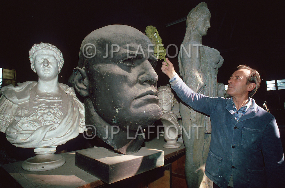 """April 27, 1990, Rome, Italy. Photographing for the book """"One day in the life of Italy"""", an exploration of Rome. In Cinecitta, at the D'Angelis Sculpture warehouse, props such as the bust of Mussolini are stored. A man dusts statues."""